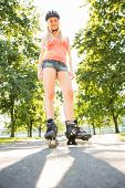 Casual smiling blonde standing in inline skates on pathway in a park