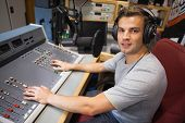 Handsome smiling radio host moderating in studio at college