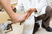 Low section of doctor testing achilles heel of patient