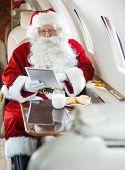Man in Santa costume using digital tablet in private jet