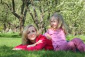 Daughter Has Leant Elbows On Mother Lying On Grass In Park