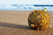 a golden christmas ball on the sand of a beach