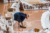 MARAS, PERU - JULY 23: woman working at Maras salt mines in the peruvian Andes at Cuzco Peru on july