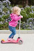 Toddler Girl On A Scooter In A Park