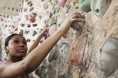 Determined young woman climbing up climbing wall