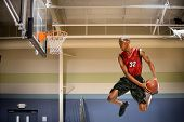 stock photo of slam  - African American basketball player in action in indoor court - JPG