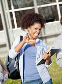 Portrait of playful female student holding books while gesturing loser sign on college campus