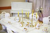 Table with set of porcelain dishes and candles and beautiful white piano in empty room.