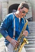 Young saxophonist plays on her sax with bright emotions in the street. Serbia.