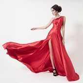 Young beauty woman in fluttering red dress. White background.