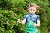 image of bolero  - Little pretty girl plays with white dandelion in summer park - JPG