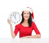 christmas, x-mas, winter, happiness concept - smiling woman in santa helper hat with clock showing 1