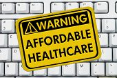 picture of mandate  - Computer keyboard keys with warning sign with words Affordable Healthcare Warning of Affordable Healthcare - JPG