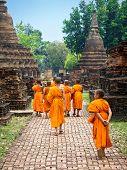 Novice Buddhist Monks Walking Among Ruins in Sukhothai, Thailand