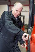 Man changing a tyre of a forklift, putting force on a torque wrench, tightening the wheel nuts.