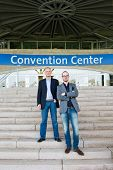 Two attendees of a congress at a trade fair posing on the steps leading to the front entrance of the