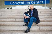 Businessman is attending a convention and sits in front of the entrance of the convention center