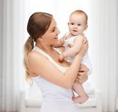 family, child and happiness concept - happy mother with adorable baby