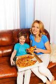 Laughing boy and mother eating pizza on the sofa