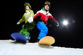 Two snowboarders ready to slide at night