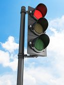 Traffic lights - all three lights are on in front of blue sky