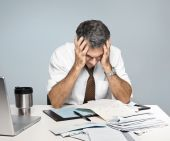 stock photo of sad man  - Man at desk in shirt and tie holding his head and worrying about money and the economy - JPG