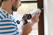 stock photo of guns  - Man applying silicone sealant with caulking gun - JPG