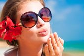 portrait of young woman in sunglasses blowing an air kiss on beach