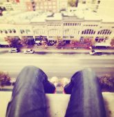 stock photo of instagram  - legs hanging over a tall building done with a retro vintage instagram filter - JPG