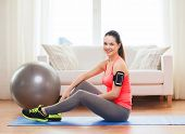 fitness, sportm home and dieting concept - smiling teenage girl with armband execising at home