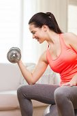 fitness, home and diet concept - smiling girl exercising with fitness ball and dumbbells at home