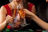 pic of gambler  - Gamblers drinking a glass of champagne by a table - JPG