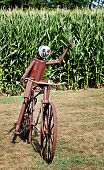 stock photo of metal sculpture  - A metal sculpture of a bicycle and rider waves to passerbys - JPG