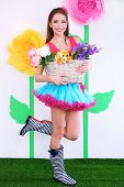 Beautiful young woman in petty skirt holding basket of flowers on decorative background
