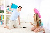 Couple fighting together with pillows on home interior background