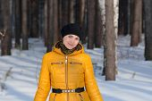 Woman in black beret b yellow jacket on forest background