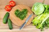 Heart shape of chopped herbs  and fresh vegetables, on wooden background