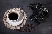Coffee cup, vintage camera and old blank photos, on wooden background