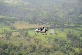 stock photo of gyrocopter  - Autogyro flying above the tropical landscape in Costa Rica - JPG