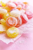 Sweet  multicolor candies on paper, on color background