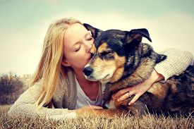 pic of hug  - a young woman and her German Shepherd dog are laying outside in the grass and she is lovingly hugging and kissing him. VIntage style color.