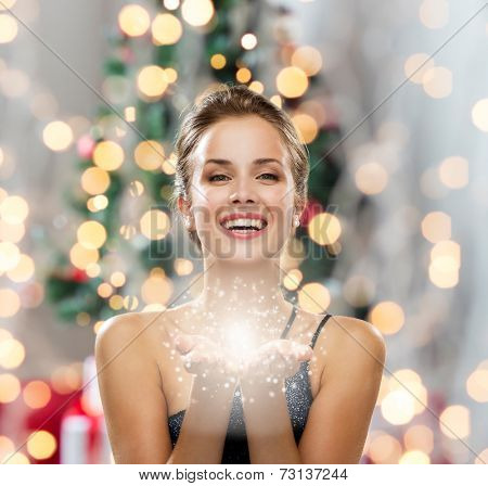 people, holidays and magic concept - laughing woman in evening dress holding something over christma poster