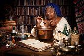 Vintage alchemist adding herbs to a smoking kettle