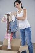 stock photo of filipina  - Young woman piling clothes into a cardboard box - JPG