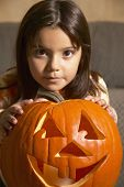 Young Hispanic girl with Jack-o-Lantern
