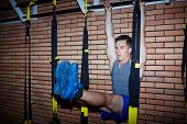 Young guy having workout on facility over brick wall in sports gym