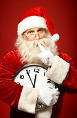 picture of shhh  - Santa holding Christmas clock and making shhh gesture while looking at camera - JPG