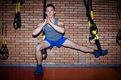 Young guy doing exercises for leg muscles over brick wall in sports gym