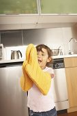 Young girl wearing oven mitts