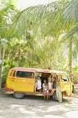 Family posing for the camera with van in tropical setting